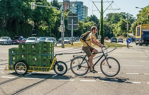 Man Driving Bike With Cargo Trailer